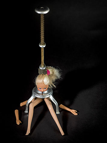 picture of Barbie crushed by a cooking utensil shot in studio Halet with a Mamiya medium format digital back Phase One