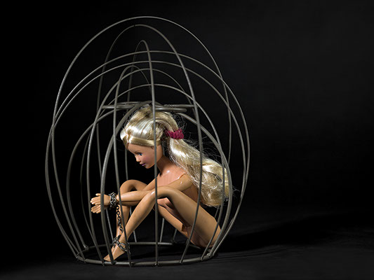 creative picture of Barbie chained in a cage shot in studio Halet with a Mamiya medium format digital back Phase One