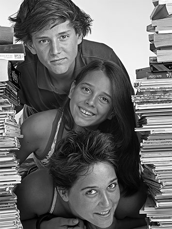 black and white portrait of a young man and two girls lying on each other surrounded by comic books column copyright Claude HALET