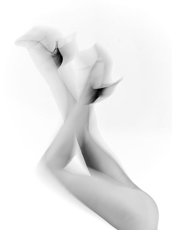 Naked and blurred female legs in the air feet are shod with high heels on white background shot in studio Halet with a Mamiya medium format