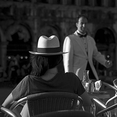 black and white photo on the St. Mark's Square at Caffè Florian a young lady sitting back with a clear cap shot by Claude Halet with a NIKON D3X